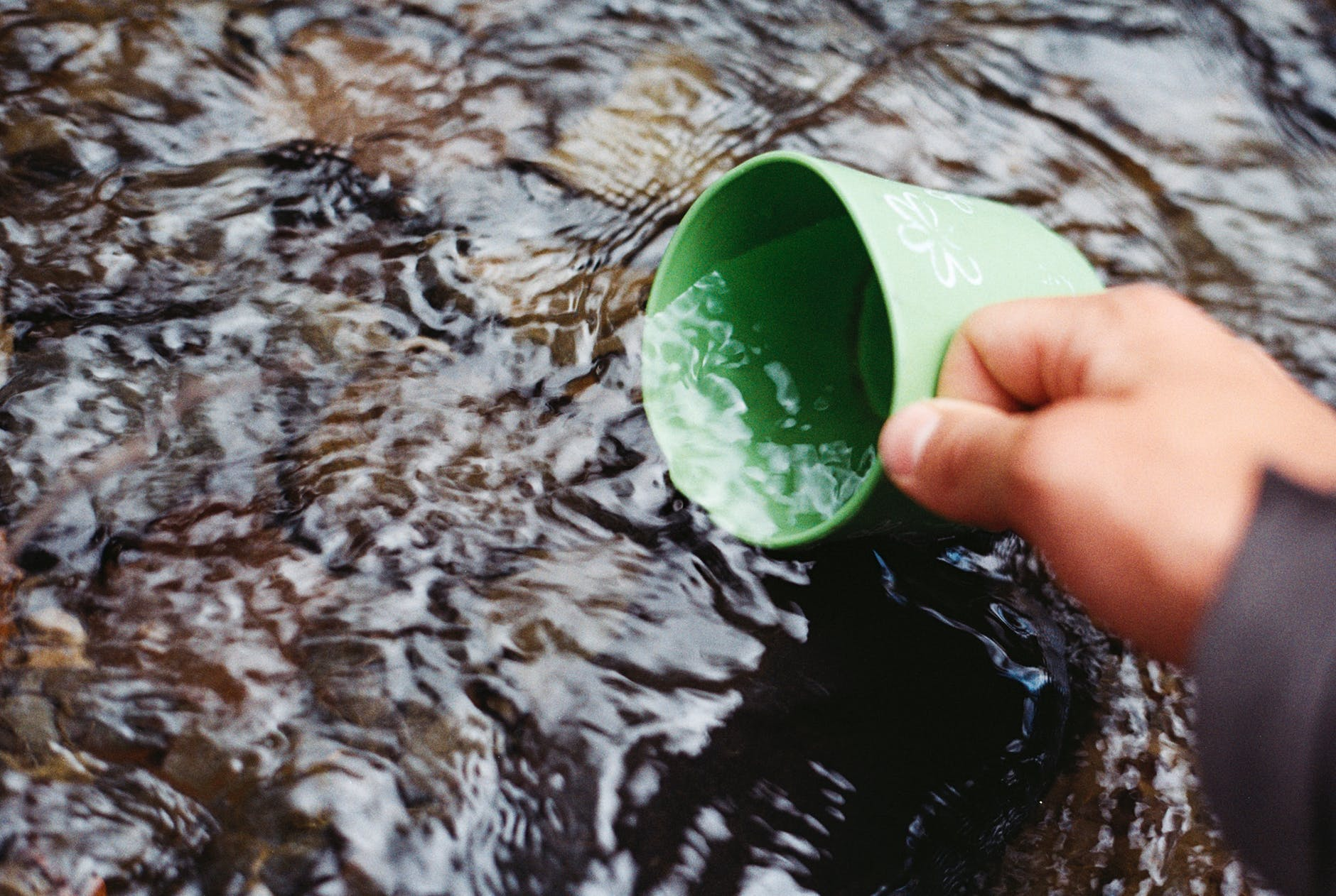 A person filling a cup with water from a mountain stream