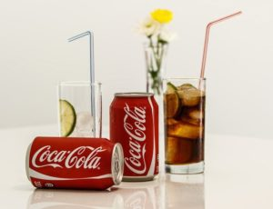 2 CocaCola can drink with Two glass of soda